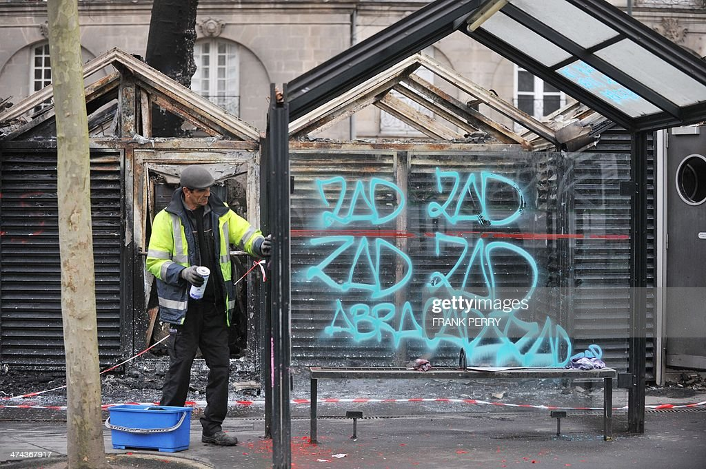 A municipal agent removes graffiti reading 'ZAD-zone to be defended' from a tramway station in Nantes, western France, on February 23, 2014 a day after protesters stage a demonstration against plans to build the Notre-Dames-des-Landes airport for the French city of Nantes. Protesters smashed shop windows on February 22 and hurled paving stones at police, who answered with tear gas and rubber bullets. Tens of thousands of protesters against building the airport on protected swampland swarmed the western city's Petite Hollande square, the latest in a string of demonstrations against the pet project of Prime Minister Jean-Marc Ayrault. AFP PHOTO/FRANK PERRY
