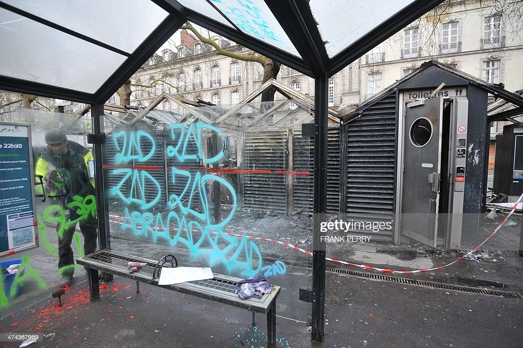 A municipal agent removes graffiti reading 'ZAD-zone to be defended' from a tramway station in Nantes, western France, on February 23, 2014 a day after protesters stage a demonstration against plans to build the Notre-Dames-des-Landes airport for the French city of Nantes. Protesters smashed shop windows on February 22 and hurled paving stones at police, who answered with tear gas and rubber bullets. Tens of thousands of protesters against building the airport on protected swampland swarmed the western city's Petite Hollande square, the latest in a string of demonstrations against the pet project of Prime Minister Jean-Marc Ayrault.