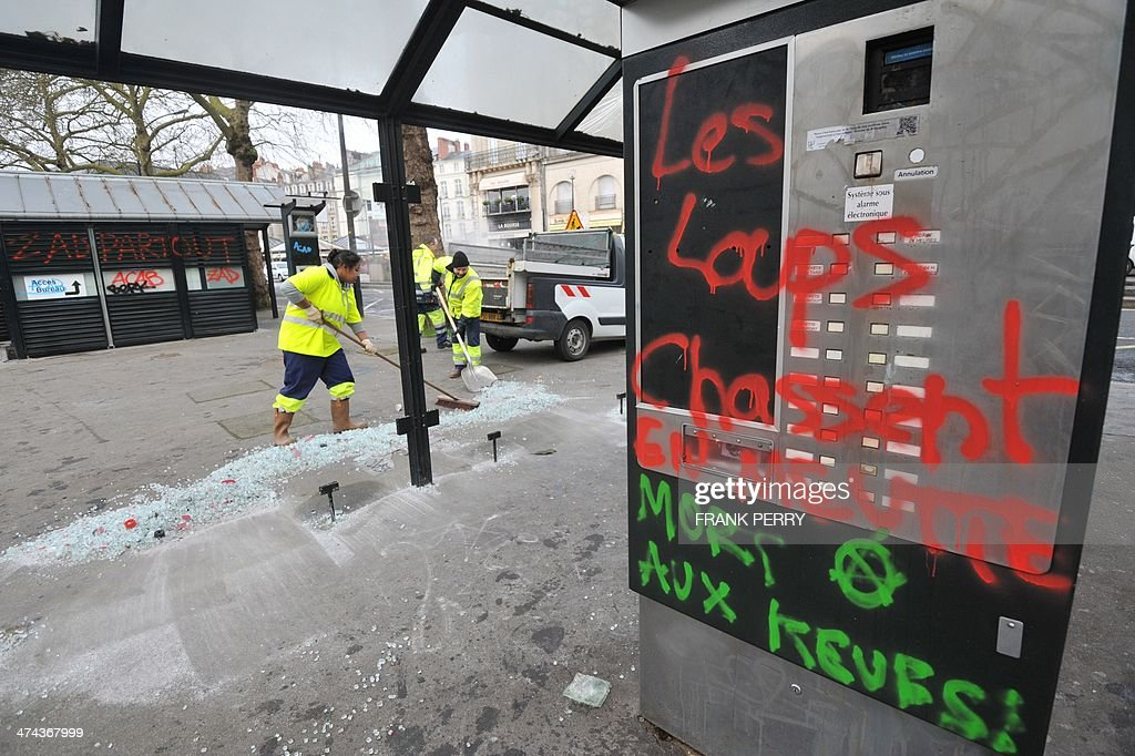 Municipal agents clean debris at a tramway station in Nantes, western France, on February 23, 2014 which was damaged by protesters opposed to plans to build the Notre-Dames-des-Landes airport for the French city of Nantes. Protesters smashed shop windows on February 22 and hurled paving stones at police, who answered with tear gas and rubber bullets. Tens of thousands of protesters against building the airport on protected swampland swarmed the western city's Petite Hollande square, the latest in a string of demonstrations against the pet project of Prime Minister Jean-Marc Ayrault. Graffiti read 'Wolves hunt in pack' and 'Death to the police'. AFP PHOTO/FRANK PERRY