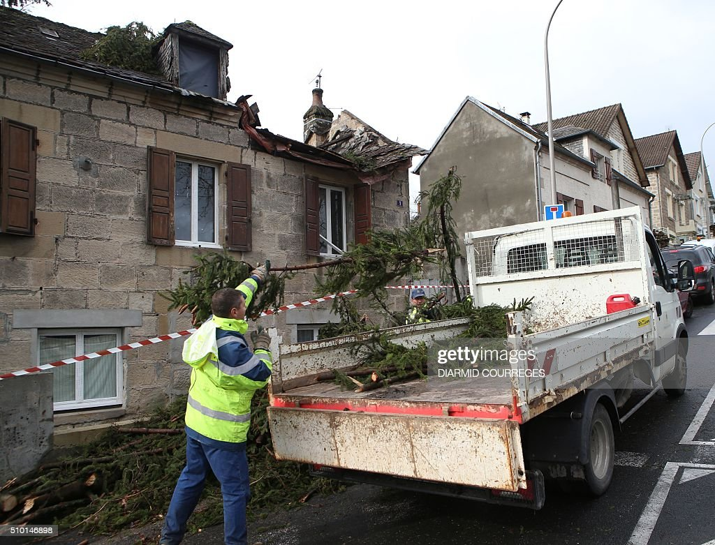 A municipal employee collects branches after a tree fell onto a house overnight on February 14, 2016 in Brive-la-Gaillarde, southwestern France, after a small tornado hit the town. About 15,000 homes were still without power Fabruary 14, including 3,000 in the Landes department and 3,000 in the Pyrenees-Atlantiques, after a storm raged through the southwest overnight. / AFP / DIARMID COURREGES