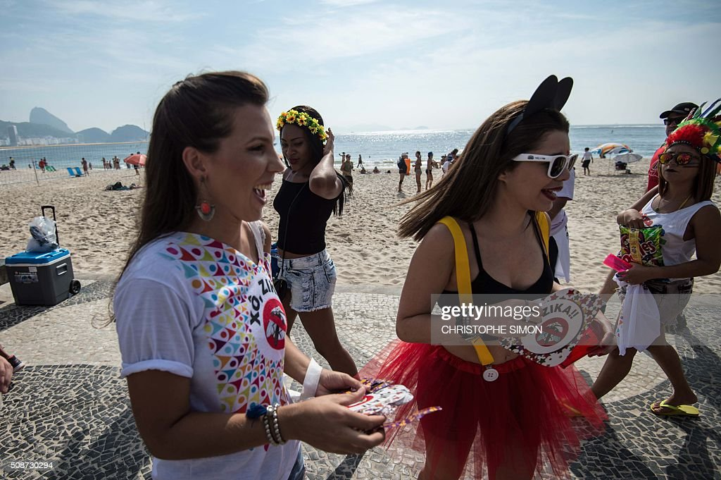A municipal employee (L) gives pamphlets containing information about the Zika virus to revellers along Copacabana beach in Rio de Janeiro, Brazil, on February 6, 2016. Carnival weekend got rolling in Rio de Janeiro, giving the city a chance to wiggle its hips and shake off worries over Zika and the economy. Like the rest of Brazil, Rio de Janeiro is struggling to respond to fears that the mosquito-transmitted Zika virus causes microcephaly, a horrific birth defect in babies. AFP PHOTO / Christophe SIMON / AFP / CHRISTOPHE SIMON