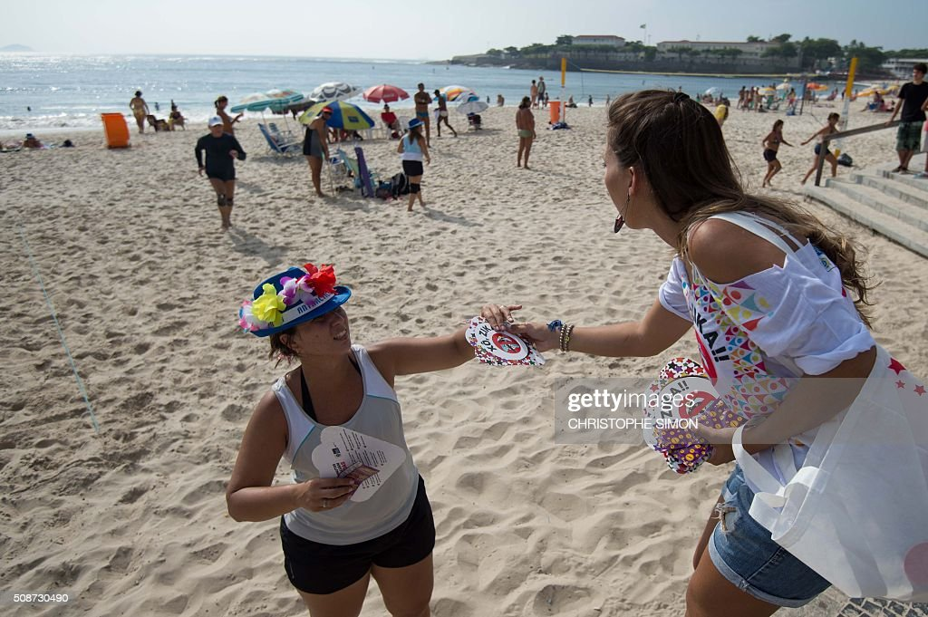 A municipal employee (L) gives pamphlets containing information about the Zika virus to a reveller as part of a prevention campaign at Copacabana beach in Rio de Janeiro, Brazil, on February 6, 2016. Carnival weekend got rolling in Rio de Janeiro, giving the city a chance to wiggle its hips and shake off worries over Zika and the economy. Like the rest of Brazil, Rio de Janeiro is struggling to respond to fears that the mosquito-transmitted Zika virus causes microcephaly, a horrific birth defect in babies. AFP PHOTO / Christophe SIMON / AFP / CHRISTOPHE SIMON