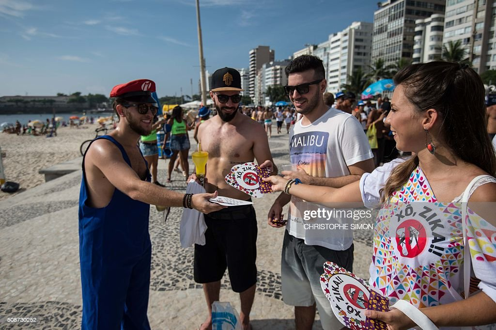 A municipal employee gives pamphlets out to revellers containing information about the Zika virus, along Copacabana beach in Rio de Janeiro, Brazil, on February 6, 2016. Carnival weekend got rolling in Rio de Janeiro, giving the city a chance to wiggle its hips and shake off worries over Zika and the economy. Like the rest of Brazil, Rio de Janeiro is struggling to respond to fears that the mosquito-transmitted Zika virus causes microcephaly, a horrific birth defect in babies. AFP PHOTO / Christophe SIMON / AFP / CHRISTOPHE SIMON
