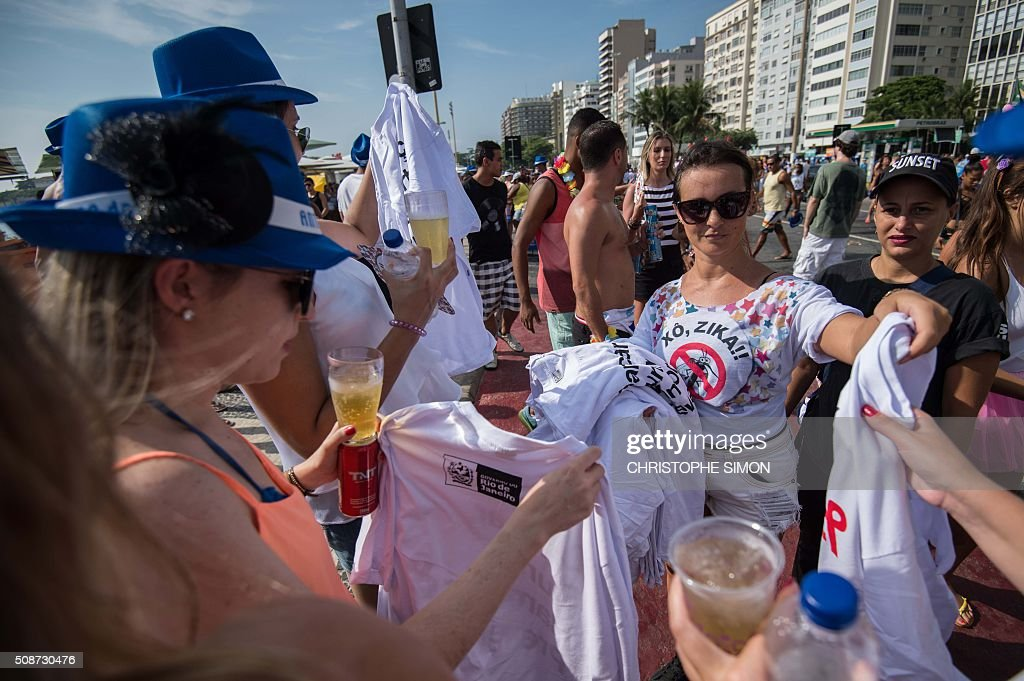 A municipal employee (R) gives t-shirts and pamphlets containing information about the Zika virus to revellers as part of a prevention campaign at Copacabana beach in Rio de Janeiro, Brazil, on February 6, 2016. Carnival weekend got rolling in Rio de Janeiro, giving the city a chance to wiggle its hips and shake off worries over Zika and the economy. Like the rest of Brazil, Rio de Janeiro is struggling to respond to fears that the mosquito-transmitted Zika virus causes microcephaly, a horrific birth defect in babies. AFP PHOTO / Christophe SIMON / AFP / CHRISTOPHE SIMON
