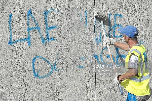 A municipal employee repaints a wall covered by a graffiti reading 'Labrune go away' claiming the resignation of the OM President Vincent Labrune and...