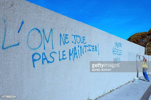 A municipal employee repaints a wall covered by a graffiti reading 'OM is not striving for relegation' claiming the resignation of the OM President...