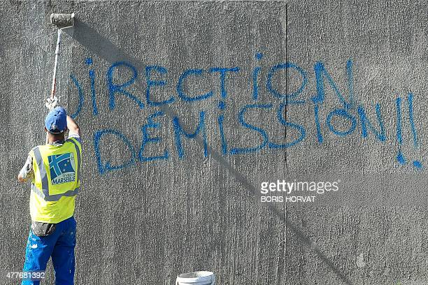 A municipal employee repaints a wall covered by a graffiti reading 'management resignation' claiming the resignation of the OM President Vincent...