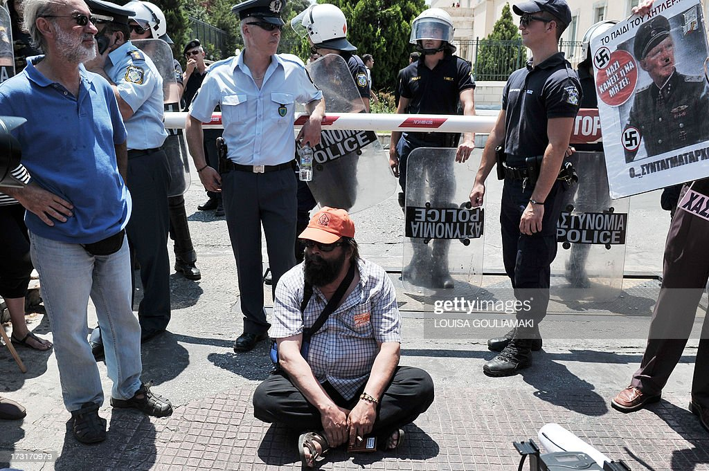 A municipal employee sits in front of the Greek parliament in Athens, during their protest rally on July 9, 2013. Greek municipal workers went on strike for the second consecutive day on Tuesday, protesting against job cuts enacted by the government in return for promised EU-IMF rescue loans.