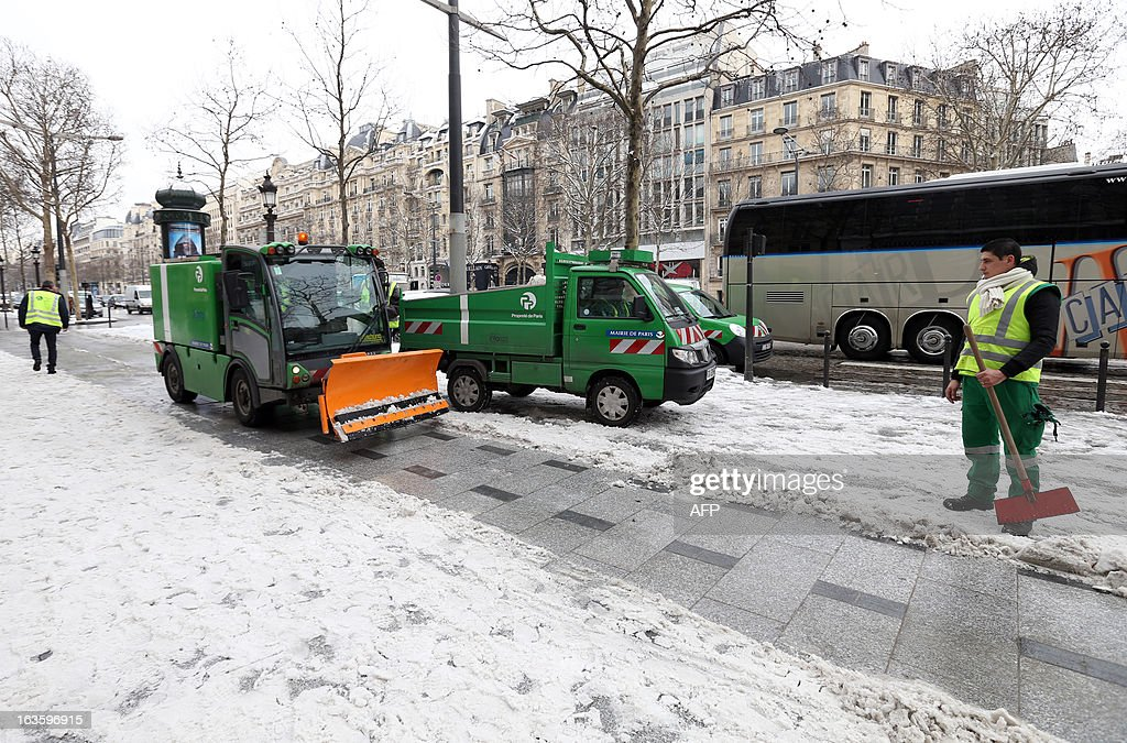 A municipal employee stands as a snow plough clears the snow from a pavement on March 13, 2013 in Paris. Blizzard-like conditions, coming only eight days before the official start of spring, knocked out power to thousands of people in France and left motorists stranded in their cars. AFP PHOTO / THOMAS SAMSON
