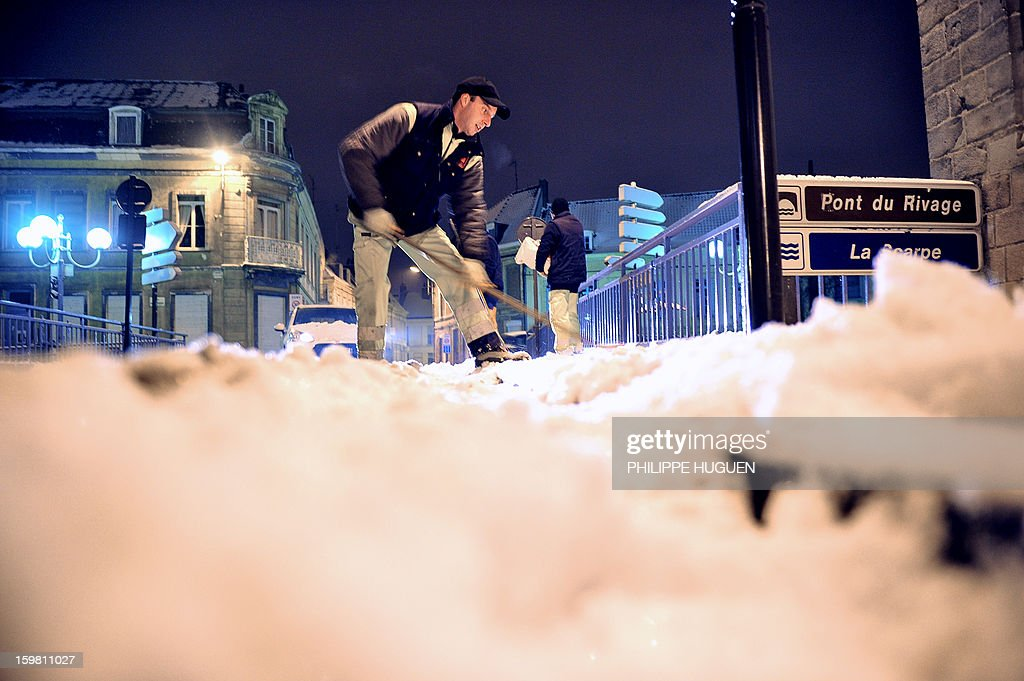 Municipal employees remove snow from the sidewalks a day after heavy snowfalls on January 21, 2013, in Douai, northern France. With up to 20 centimetres (eight inches) of snow falling in the most-affected areas over the weekend, more than a quarter of France's regions were on alert and the weather service warned that more snowfall was expected overnight.