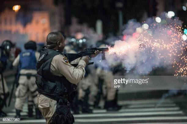 TOPSHOT A municipal guard in riot gear fires rubber bullets at protesters during a national strike against the government's social welfare reform...