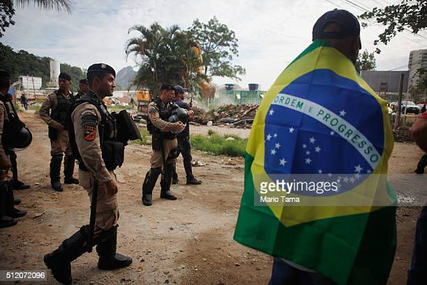Municipal Guard police keep watch as a resident stands wearing a Brazilian flag during the demolition of the residents association building in the...