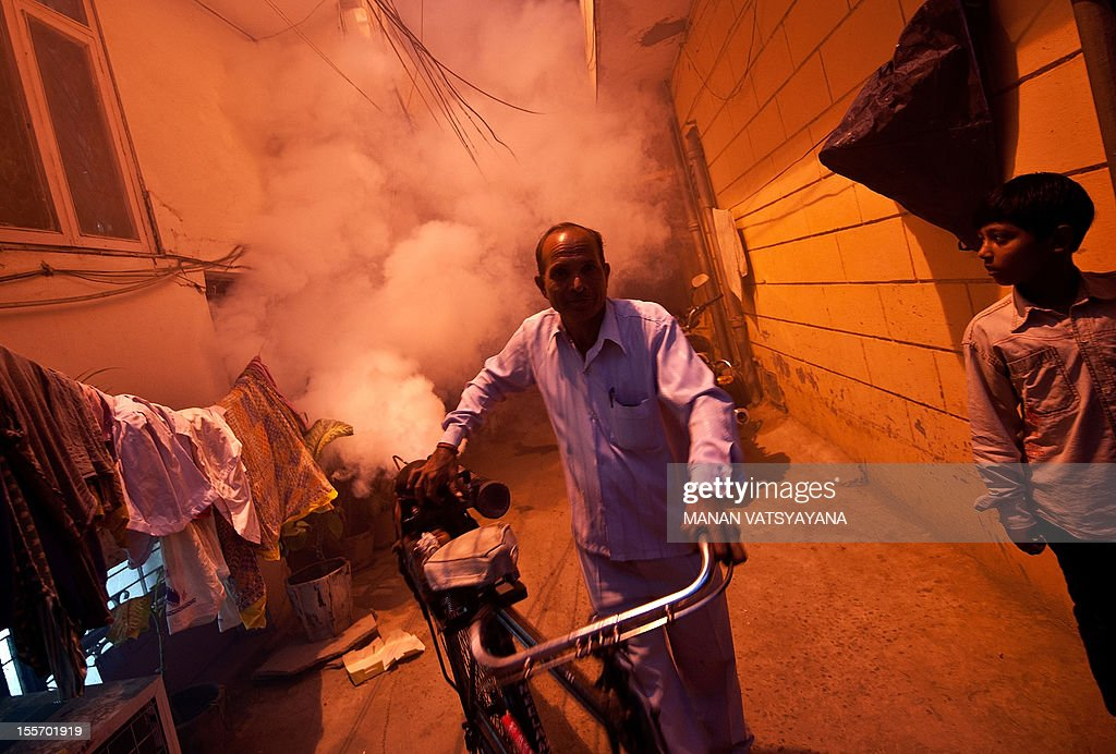 A municipal health worker, transporting his fogging machine on a bicycle, fumigates a neighbourhood against mosquitoes in New Delhi on November 7, 2012. Dengue continued to spread in the Indian capital with 39 fresh cases being reported November 7, taking the toll of people detected with the mosquito-borne disease this season to 1,288, according to Press Trust of India (PTI).