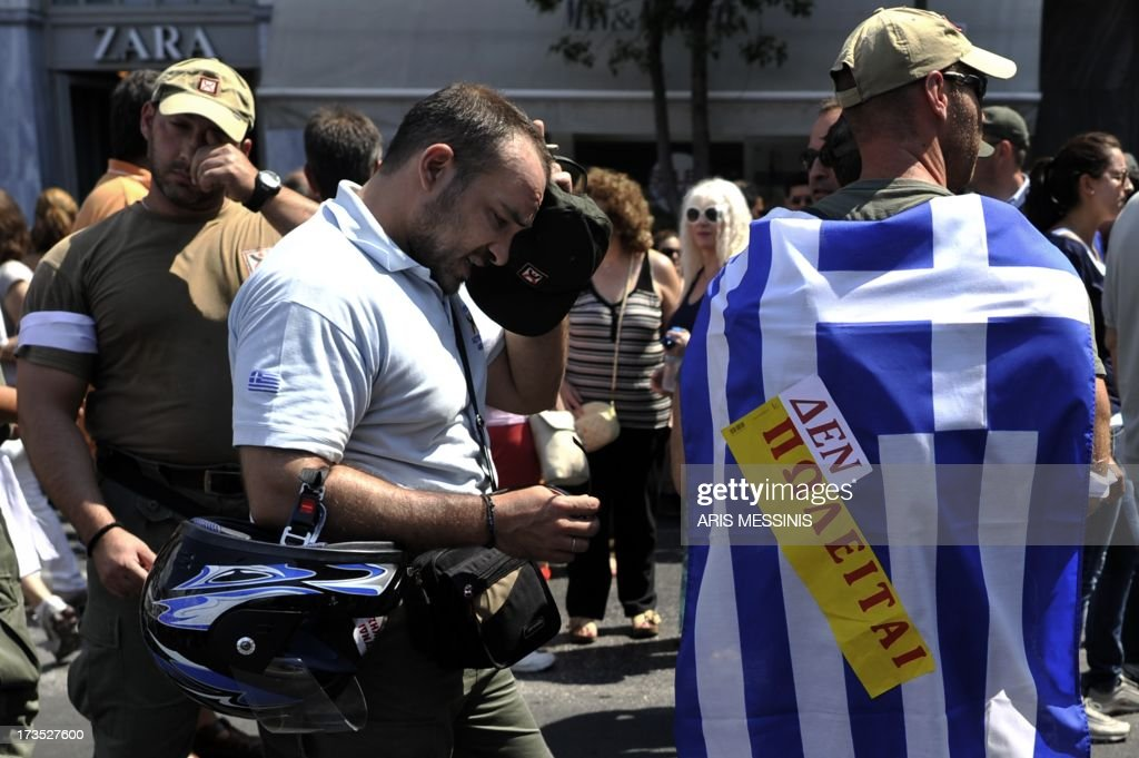 A municipal police member wears a Greek flag, reading: 'Not for Sale', suring a demonstration as part of a general strike in Athens on July 16, 2013. A general strike gripped Greece on July 16 for the fourth time this year as unions railed at fresh austerity measures the government is imposing in order to keep receiving EU-IMF loans. Thousands of protesters gathered ahead of rallies to be held later in the day, with 16,000 demonstrators coming out in Athens and 7,000 in Thessaloniki, according to police.