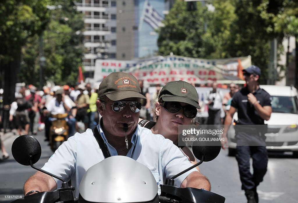 Municipal police members take part in a protest near the Greek parliament in Athens on July 9, 2013. Greek municipal workers went on strike for the second consecutive day on today, protesting against job cuts enacted by the government in return for promised EU-IMF rescue loans.