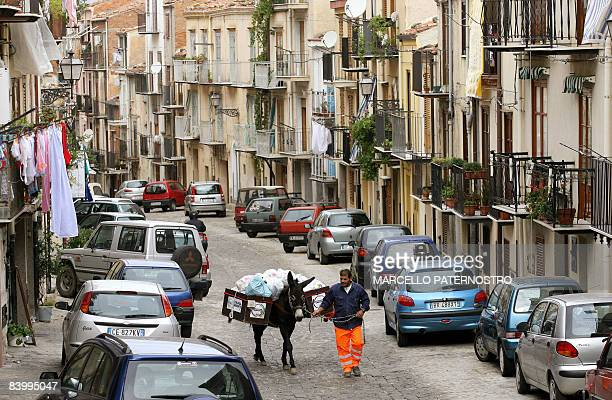 A municipal worker and his donkey collect the trash in the streets of Castelbuono a town in the province of Palermo Sicily 30 October 2007 The...