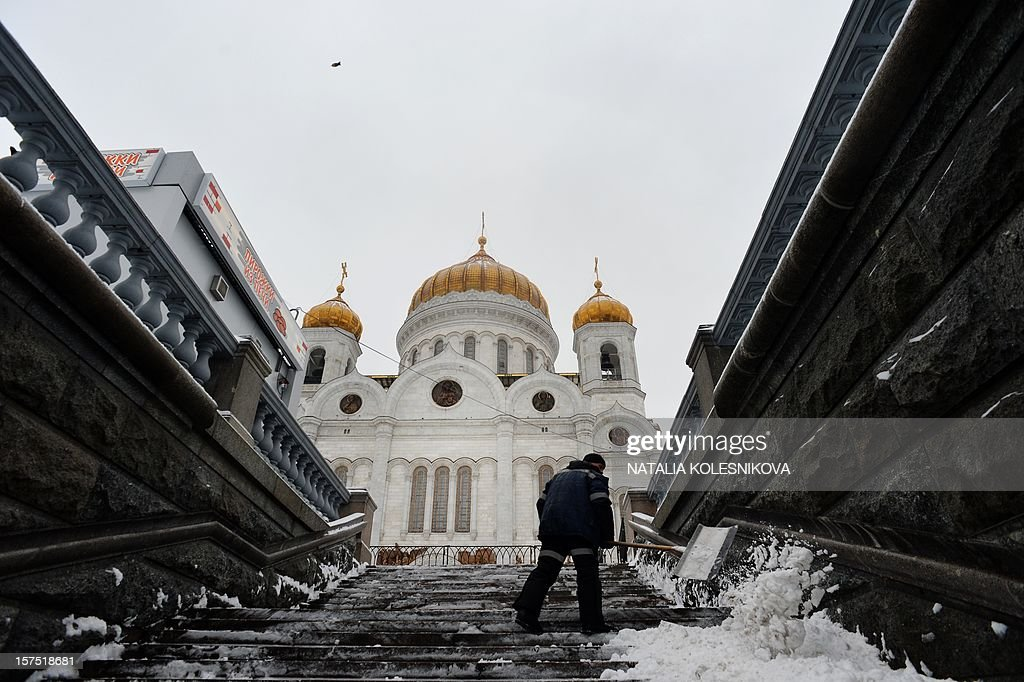A municipal worker cleans snow on the pedestrian Patriarchal Bridge across the Moskva River just outside the Christ the Saviour Cathedral in Moscow, on December 4, 2012. Moscovites woke up today to a thick blanket of snow covering the Russian capital.The temperatures in Moscow reached today 1C (34 F), but due to high humidity and wind, weather experts said it would feel more like - 3C (25 F).