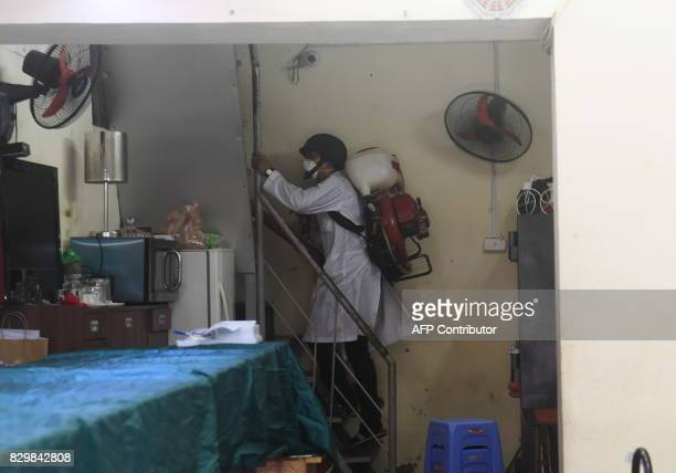 A municipal worker climbs the stairs as he sprays chemicals to kill mosquitos at a residential home in downtown Hanoi on August 11 2017 as...