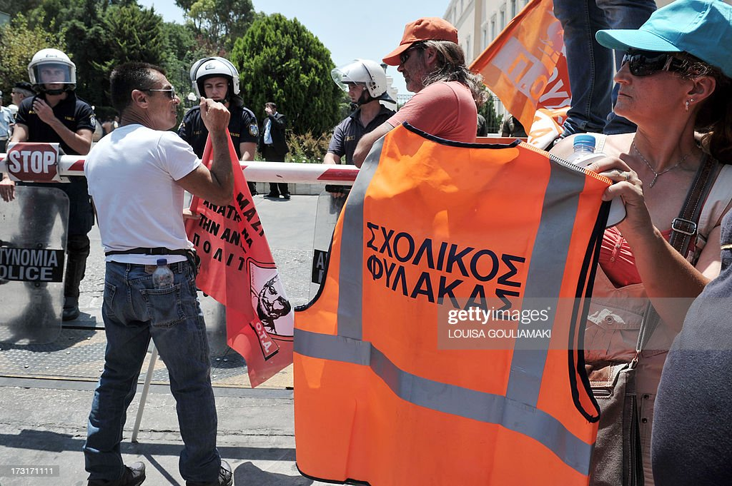 A municipal worker displays a work jacket reading 'school guard' in front of the Greek parliament during a protest in Athens on July 9, 2013. Greek municipal workers went on strike for the second consecutive day on today, protesting against job cuts enacted by the government in return for promised EU-IMF rescue loans.