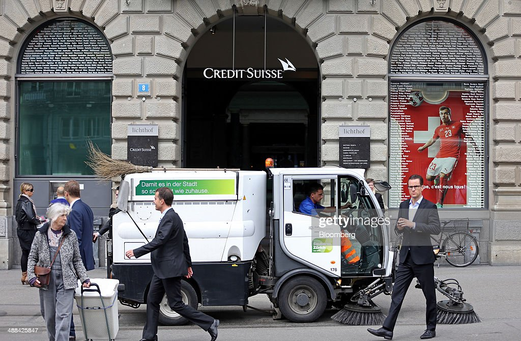 A municipal worker drives a road sweeper past pedestrians outside Credit Suisse Group AG's headquarters in Zurich, Switzerland, on Tuesday, May 6, 2014. Credit Suisse is close to resolving a U.S. tax-evasion probe with an agreement that might include a penalty of more than $1 billion, after creating a separate entity last year to house the businesses involved. Photographer: Philipp Schmidli/Bloomberg via Getty Images