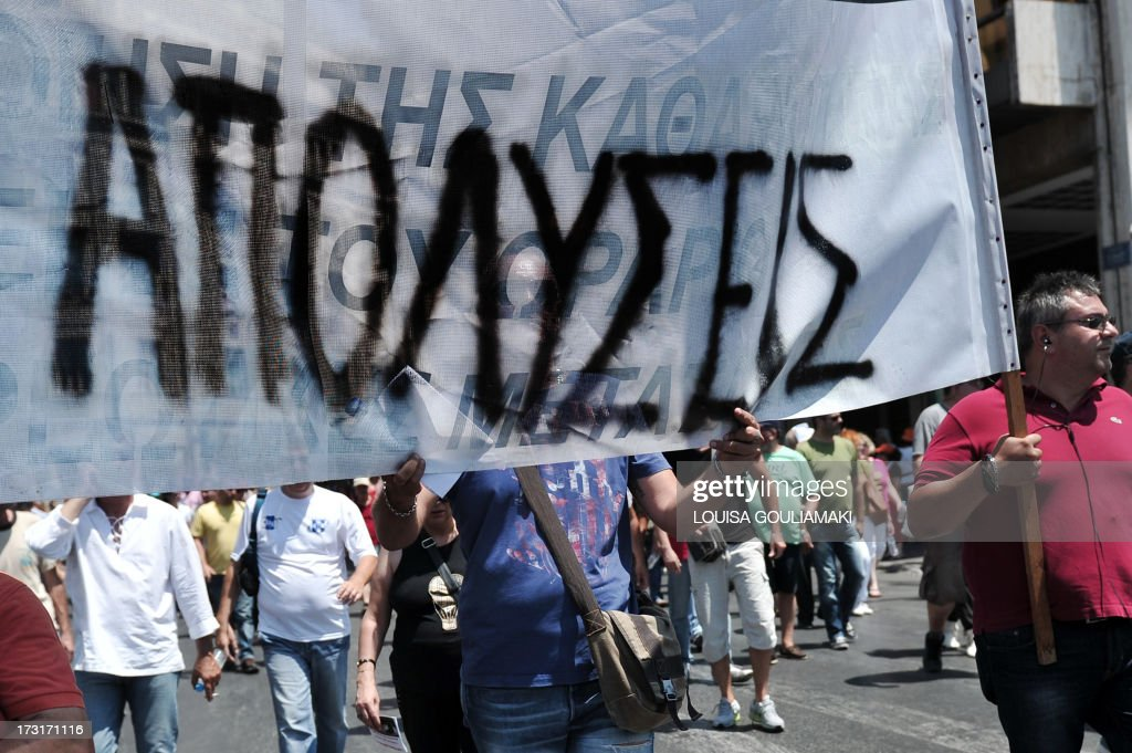 A municipal worker holds a banner reading 'layoffs' during a protest near the Greek parliament in Athens on July 9, 2013. Greek municipal workers went on strike for the second consecutive day on today, protesting against job cuts enacted by the government in return for promised EU-IMF rescue loans.