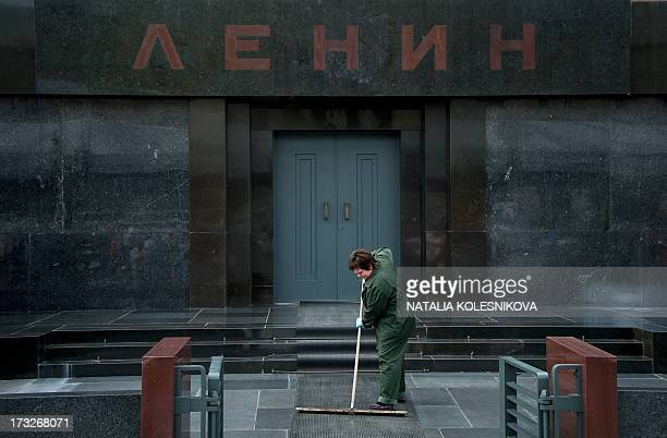 A municipal worker mops the entrance to Soviet founder Vladimir Lenin's Mausoleum on the Red Square in Moscow on July 11 2013 AFP PHOTO / NATALIA...