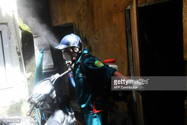 A municipal worker sprays chemicals to kill mosquitos at a residential home in downtown Hanoi on August 11 2017 as authorities make efforts to stop...