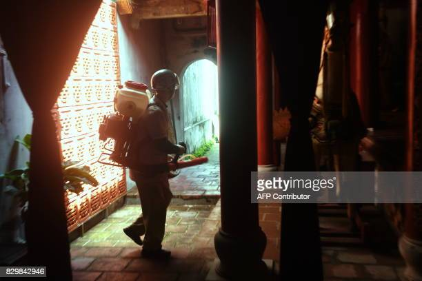 A municipal worker sprays chemicals to kill mosquitos at a temple in downtown Hanoi on August 11 2017 as authorities make efforts to stop the spread...