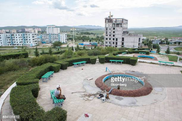 A municipal worker takes a break in a park as housing stands in the background in Darkhan Mongolia on Monday Aug 14 2017 Mongolia desperate to make...