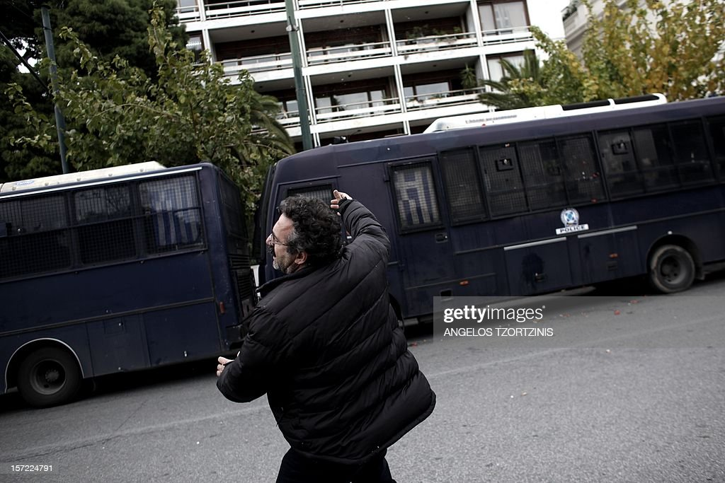 A municipal worker throws an egg at the Interior Ministry during a demonstration against austerity measures and expected layoffs in the public sector in Athens on November 30, 2012. Germany's parliament on November 30 overwhelmingly approved billions of euros in international aid for Greece, handing a much-needed financial boost to Athens as it battles against bankruptcy. AFP PHOTO / Angelos Tzortzinis