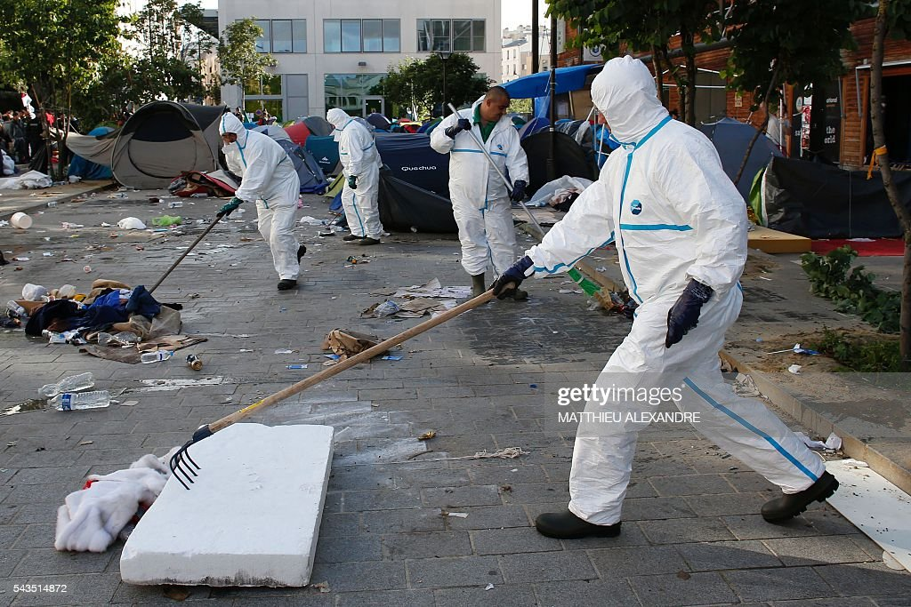 Municipal workers clean a migrants' camp after French Gendarmes evacuated it on June 29, 2016 in Paris. The police started early on June 29, 2016, the evacuation of several hundreds of migrants, from a camp at the former SNCF Hall 'Pajol'. / AFP / MATTHIEU