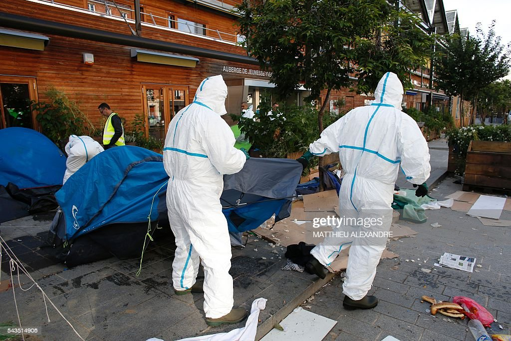 Municipal workers clean a migrants' camp after French Gendarmes evacuated it near the Pajol hall on June 29, 2016 in Paris. The police started early on June 29, 2016, the evacuation of several hundreds of migrants, from a camp at the former SNCF Hall 'Pajol'. / AFP / MATTHIEU