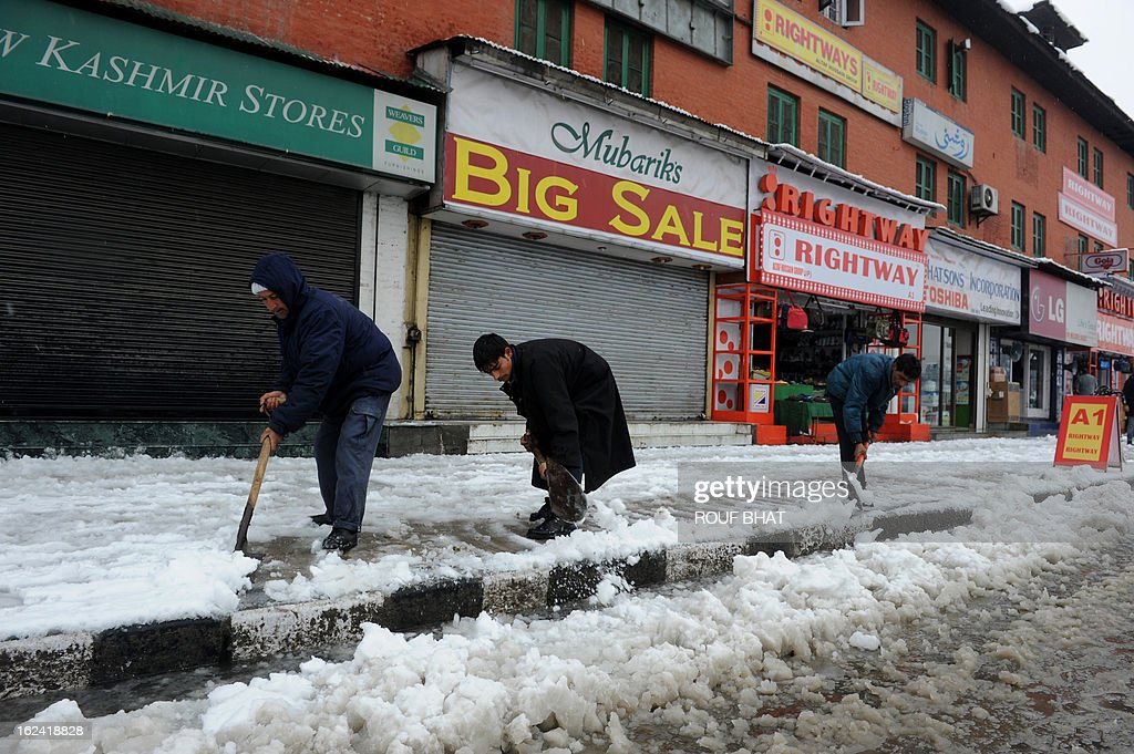 Municipal workers clear the road during a snow fall in Srinagar on February 23, 2013. The Jammu-Srinagar National Highway remained closed for the second day as fresh snowfall across Kashmir prompted authorities to issue an avalanche warning in higher reaches of the Valley. AFP PHOTO/ Rouf BHAT
