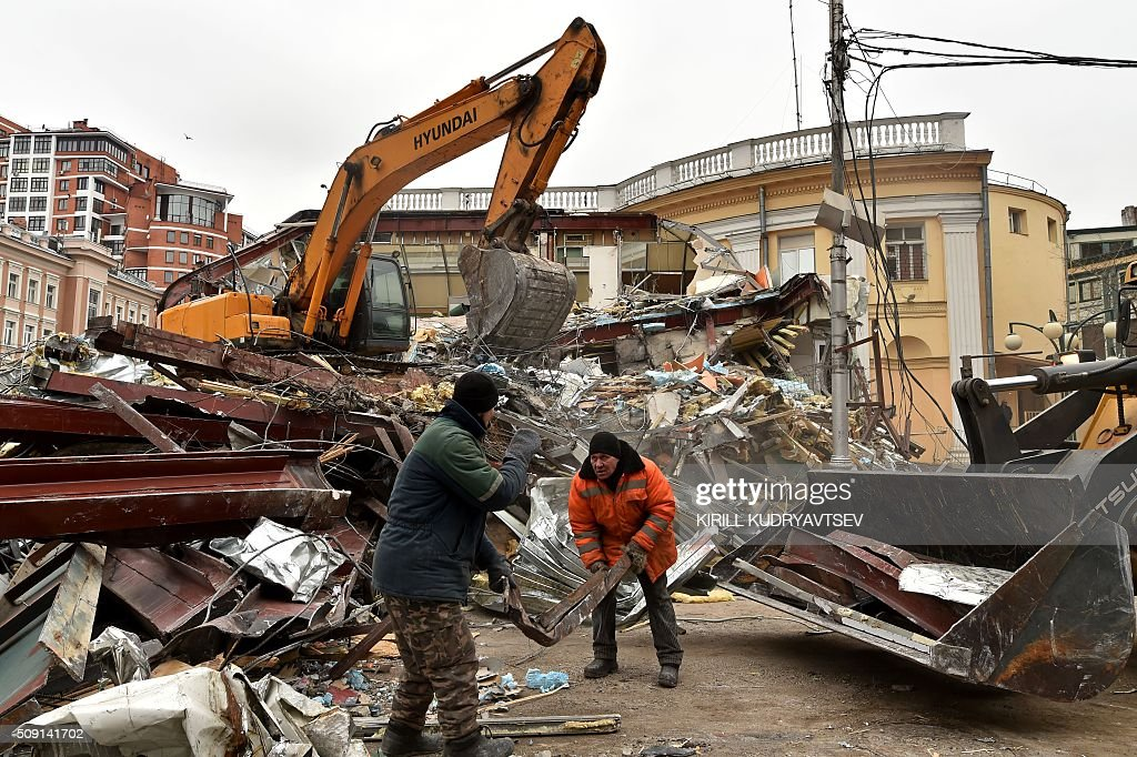 Municipal workers collect debris as an excavator knocks down a street kiosk, deemed by authorities to have been illegally built, in central Moscow on February 9, 2016. Russian authorities ordered the demolition of street kiosks built without permits in Moscow, according to local media. AFP PHOTO / KIRILL KUDRYAVTSEV / AFP / KIRILL KUDRYAVTSEV