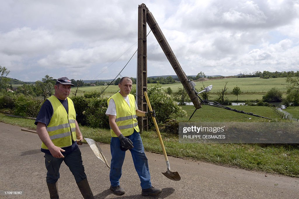 Municipal workers pass by a concrete electrical pole on June 20, 2013 that was broken by heavy winds on June 19 in the central French town of Etrochet. Heavy thunderstorms hit the Chatillon-sur-Seine area late on June 19, damaging some 150 houses, some totally. Unseasonal storms caused havoc across huge swaths of the country on June 19.