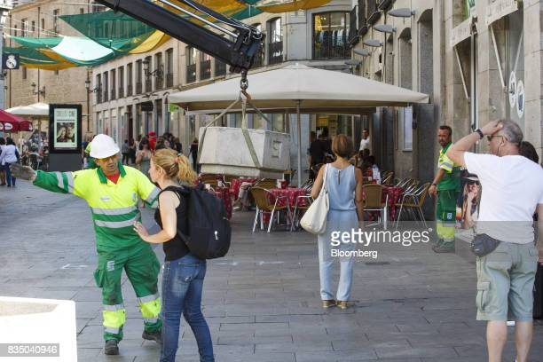 Municipal workers place street furniture near a cafe terrace on Puerta del Sol street as a security measure to prevent vehicle access in Madrid Spain...