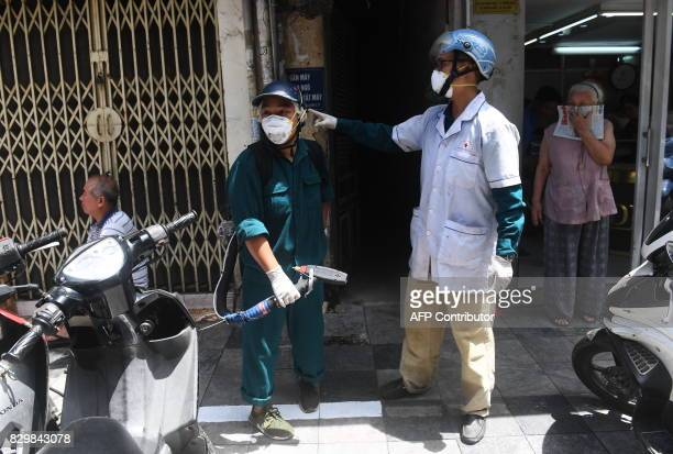 Municipal workers prepare to spray chemicals to kill mosquitos at residential homes in downtown Hanoi on August 11 2017 as authorities make efforts...