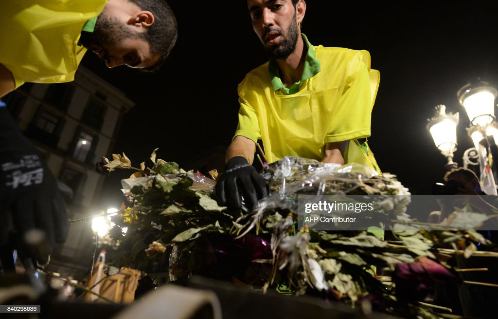 Municipal workers remove flowers from a tribute in memory of the victims of last´s week attack at the Ramblas boulevard in Barcelona, on August 28, 2017. The number of people killed in twin vehicle attacks in Spain last week rose to 16, local authorities in Barcelona said. The attacks on Las Ramblas boulevard in Barcelona and in the seaside resort of Cambrils left around 120 wounded. / AFP PHOTO / Josep LAGO