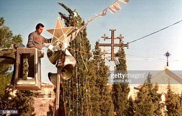 A municipality worker prepares Christmas decorations in Bethelehem's Manger Square 21 December 1994 Palestinians are preparing for the first time to...