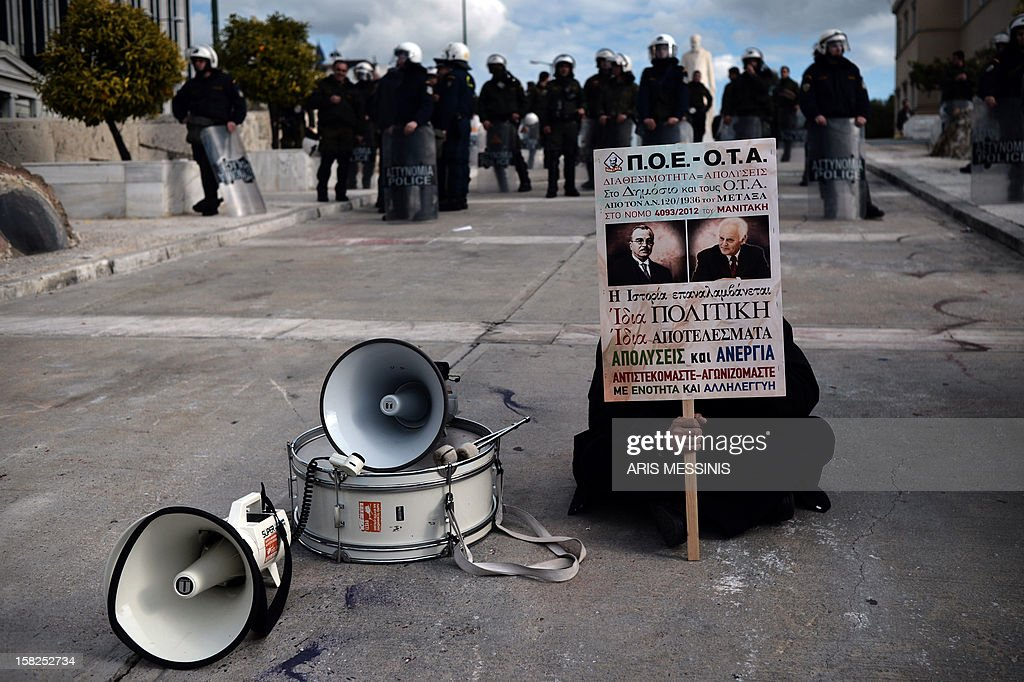 A municipality worker sits in front of anti-riot police during a demonstration held outside the Parliament in Athens on December 12, 2012. Germany and France signalled on December 12 that a Greek debt buy-back passed a critical bailout test, saying it was 'satisfactory' even though it will cost more than expected.