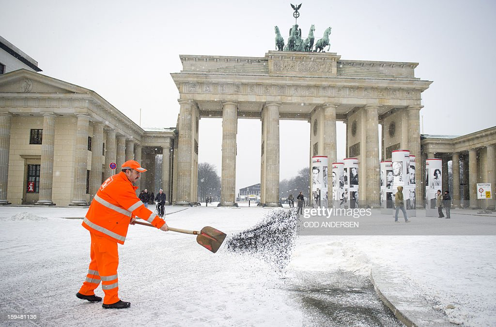 A municipality worker throws grit on the place in front of the Brandenburg Gate in Berlin on January 14, 2013. Temperature dropped over night and snow followed at daybrake in the German capital.