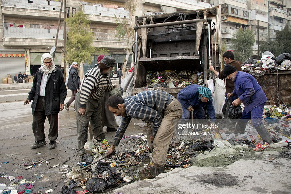 Municipality workers collect rubbish in the Aleppo neighbourhood of al-Fados on December 9, 2012. With the city's rubbish dumps out of reach due to fighting between Syrian government forces and rebel fighters, garbage is piling up in open spaces around city and power and water have shut down for the past week.