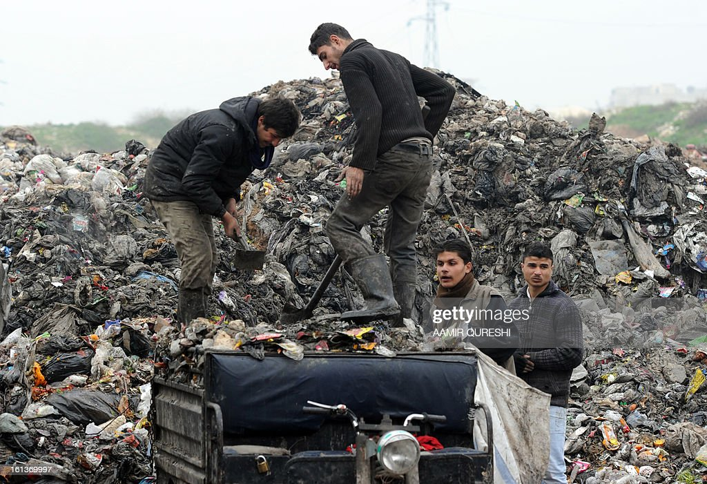 Municipality workers dump rubbish in the Saif al-Dawlah neighborhood of Aleppo on February 10, 2013. Syrian rebels launched fierce assaults on regime troops in several parts of the country, including near Deir Ezzor where they used tanks to shell an army brigade, a watchdog and activists said.