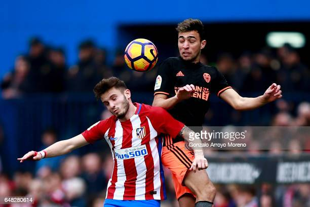 Munir El Haddadi of Valencia CF wins the header before Saul Niguez of Atletico de Madrid during the La Liga match between Club Atletico de Madrid and...