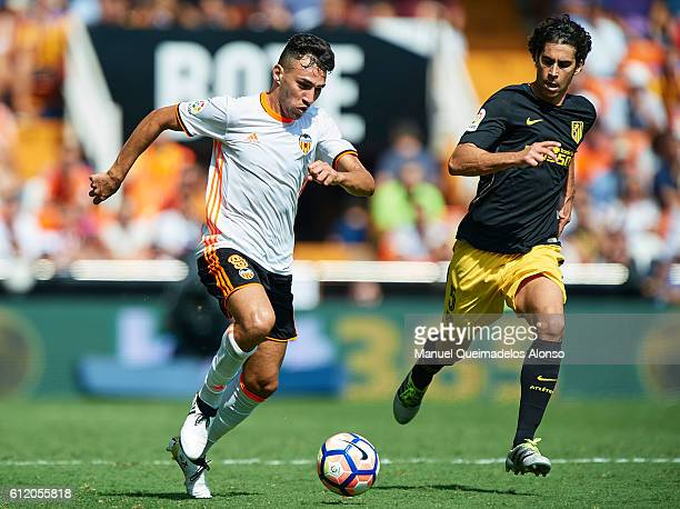 Munir El Haddadi of Valencia runs with the ball next to Tiago Cardoso of Atletico de Madrid during the La Liga match between Valencia CF and Atletico...