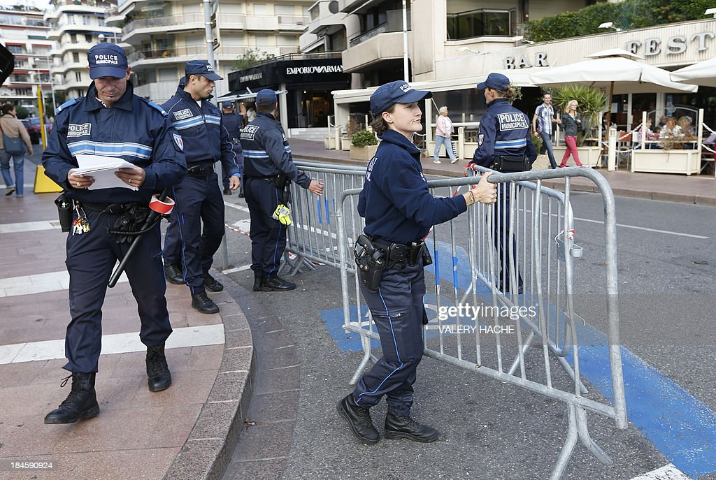 Munisipal police block access near the Carlton Hotel in the southeastern French city of Cannes on October 14, 2013 before the wedding party of a London-based Indian couple. The Carlton palace was entirely booked for several nights to accomodate guests for the wedding of Grover and Ria Dubash.