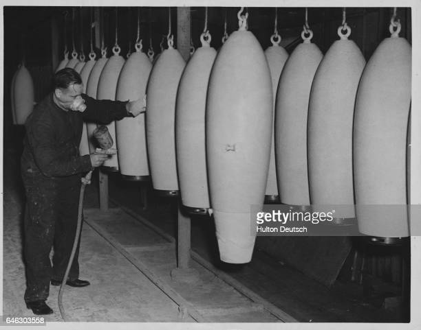 A munition worker paints a line of bombs