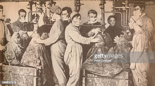 Munition Workers Wearing Respirators While Filling Sells with Trinitrotoluene circa 1916 From His Majesty The King 19101935 [Associated Newspapers...