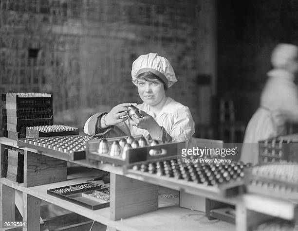A munitions worker checking shell primers