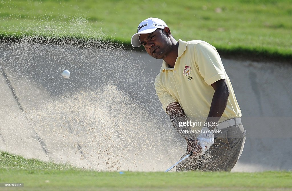 C. Muniyappa of India hits the ball out of a bunker during the Avantha Masters golf tournament in Greater Noida, on the outskirts of New Delhi, on March 15, 2013.
